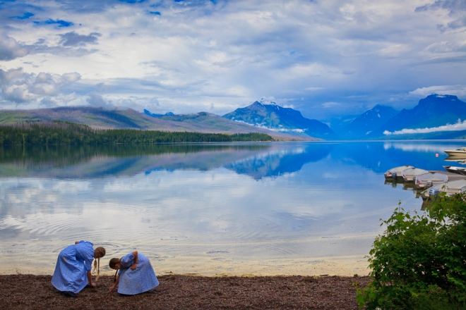Two girls skipping stones at the edge of Lake McDonald in Glacier National Park, Montana