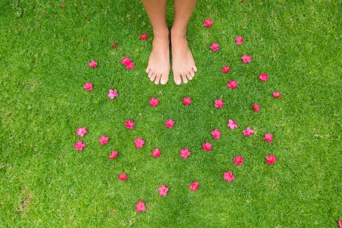 pink flowers with a happy face in the grass with bare feet, Maui, Hawaii