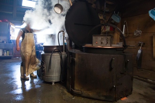 A Swiss cheese-maker working on a batch of Alpkäse by hand in the traditional manner in a giant copper kettle over a wood burning fire at their cheese-making hut above Wengen, Switzerland