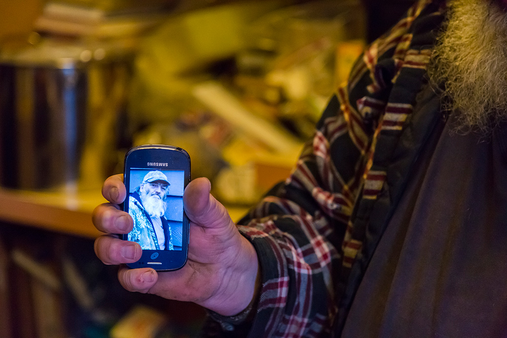 Clayton Green holding a photo on a cell phone of his brother Kevin Green, at his family's farm in Yamhill, Ore.  Photographed with a Canon 5D Mark III and a 24-105L IS USM lens.