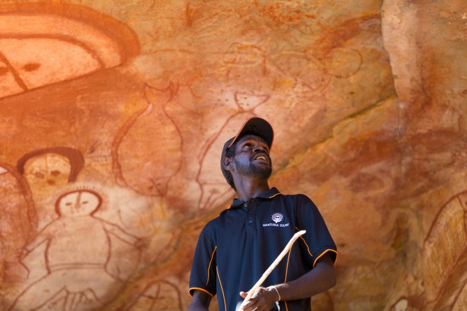 A traditional owner explains the Wandjina Rock art at Ngumbri, Raft Point, Kimberly Coast, Australia